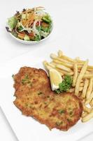 deutsch paniertes Schweineschnitzel mit Pommes frites auf weißem Studiohintergrund foto