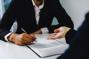 Geschäftsmann unterzeichnen Vertrag und weibliche Anwältin oder Richterin konsultieren foto
