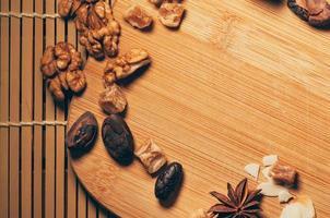 Nüsse, Früchte, Kakaobohnen und Anis auf einem Schneidebrett foto