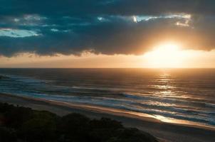 Früher Sonnenaufgang am Meeresstrand, dramatische Wolken über dem Horizont foto