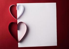 rotes Herzpapier und leer mit Anmerkungskarte auf rotem Hintergrund. foto