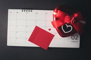 rotes Herz im 14. Februar auf dem Kalender mit herzförmiger Geschenkbox. foto