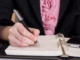 Geschäftsfrau, die Notizbuch schreibt foto