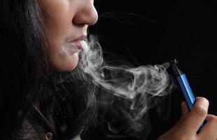 Nahaufnahme junge Frau raucht E-Zigarette auf schwarzem Hintergrund foto