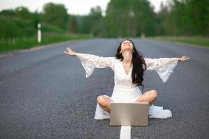 junge Frau mit Laptop auf Landstraße foto