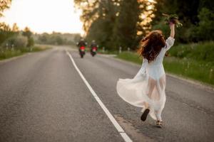 Rückansicht einer jungen Frau in einem weißen Kleid, die auf der Landstraße läuft foto