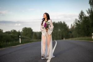 junge Frau trägt weißes Kleid auf leerer Landstraße foto
