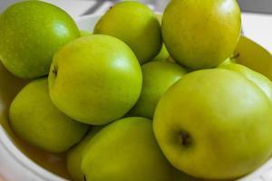 grüne saure Äpfel auf einem weißen Teller. foto