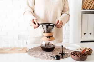 junge Frau, die Kaffee in der Kaffeekanne brüht, Kaffee in das Glas gießt foto