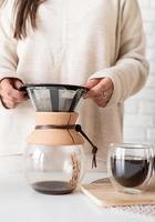 junge Frau, die Kaffee in der Kaffeekanne brüht und einen Kuchen anschneidet foto