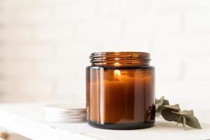 schöne brennende Kerze mit Eukalyptusblättern foto