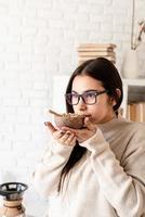 Frau, die Kaffee in der Kaffeekanne brüht und grüne Kaffeebohnen riecht foto