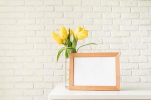 gelbe Tulpen in einer Glasvase und einem leeren Bilderrahmen foto