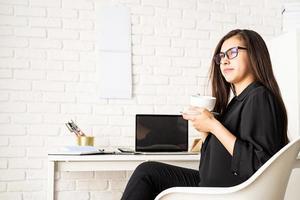 selbstbewusste brünette Geschäftsfrau, die Tee oder Kaffee trinkt foto