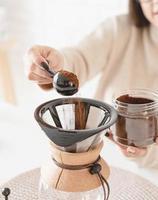 Frau, die Kaffee in einer Kanne brüht foto