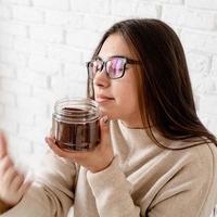 Frau, die Kaffee in der Kaffeekanne brüht und gemahlene Kaffeebohnen riecht foto