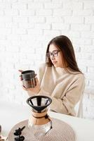 Frau, die Kaffee in der Kaffeekanne brüht foto