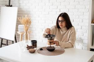 Frau, die Kaffee in der Kaffeekanne brüht und heißes Wasser in den Filter gießt foto