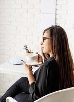 Geschäftsfrau, die im Büro arbeitet und Tee oder Kaffee trinkt foto