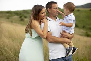 junge Familie mit süßem kleinen Jungen, der Spaß im Freien auf dem Feld hat foto