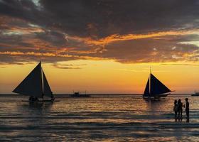 schöner tropischer sonnenuntergang mit segelbooten und touristen auf der insel boracay philippinen foto