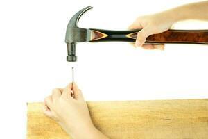 Hand, die einen Hammer schlägt, der einen Nagel schlägt foto