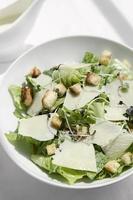 Caesar-Salat mit Parmesan und Croutons auf Holztisch foto