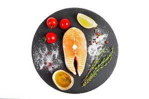 frisches Lachssteak mit Zitrone, Tomate und Olivenöl foto