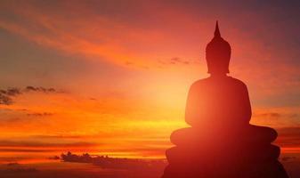 Buddha-Silhouette auf goldenem Sonnenuntergang Hintergrund Überzeugungen des Buddhismus foto