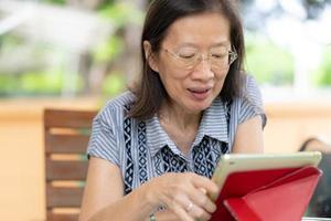 Senior asiatische Frau mit digitalem Tablet zu Hause foto