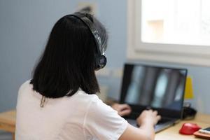 junge Frau, die während der Pandemie-Sperrung Computer benutzt, um von zu Hause aus zu warnen foto