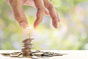 Nahaufnahme der menschlichen Hand, die eine Münze auf einen Haufen Münzen legt foto