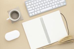 Schreibtisch-Tisch-Draufsicht mit Bürobedarf, beiger Tisch mit Kopienraum, beigefarbene Arbeitsplatzzusammensetzung, flache Lage foto