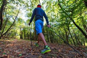 ein Mann, der Nordic Walking im Herbstwald zwischen den Blättern praktiziert foto
