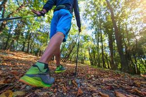 Nordic Walking zwischen den Blättern im Wald im Herbst foto
