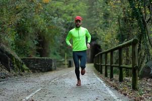 Mann Athlet läuft im Herbst auf Radweg foto