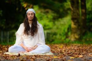 Mädchen praktiziert Yoga zwischen den Herbstblättern foto