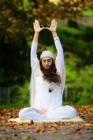 Im Herbstpark praktiziert eine junge Frau alleine Yoga foto