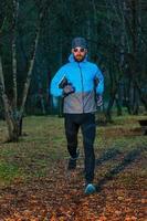 Sportler des jungen Mannes während eines Laufs im Wald foto