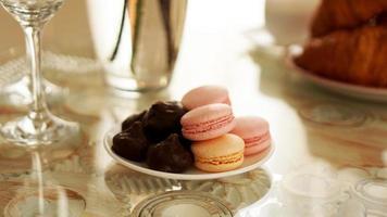 Makronen auf einem Glastisch. Süßigkeiten zum Frühstück. sonniges Foto