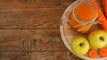 Apfel- und Karottensaft im Glas, frisches Gemüse und Obst auf Holz foto