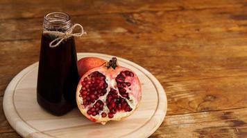 reife Granatäpfel mit Saft auf hölzernem Hintergrund. foto