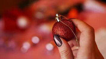 weibliche Hand hält roten Ball auf Weihnachtshintergrund foto