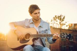 junger Mann, der Gitarre in der Stadt auf Sonnenstrahlenhintergrund spielt foto