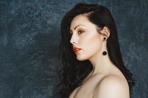 Frau mit langen Haaren, die Ohrringe auf grauem Hintergrund trägt foto
