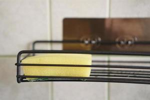 Schwamm zum Spülen von Geschirr auf Metallregal in der Küche foto