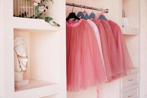 Ankleideschrank mit rosa Kleidern auf Kleiderbügel foto