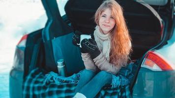 glückliches Mädchen, das auf LKW des Autos im Winterwald sitzt foto