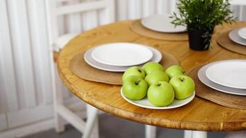 grüne Äpfel auf einem weißen Teller auf einem Holztisch foto