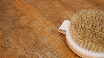 Trockenmassagebürste aus Naturmaterialien auf Holzuntergrund foto